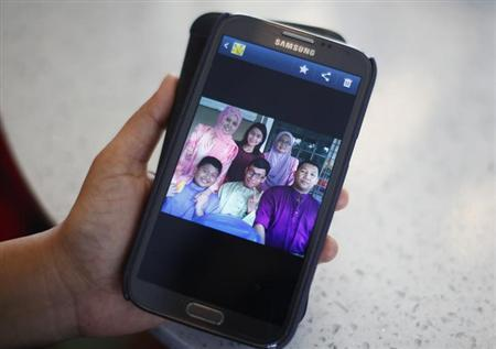 Arni Marlina, 36, a family member of a passenger onboard the missing Malaysia Airlines flight MH370, shows a family picture on her mobile phone, at a hotel in Putrajaya March 9, 2014. REUTERS/Samsul Said