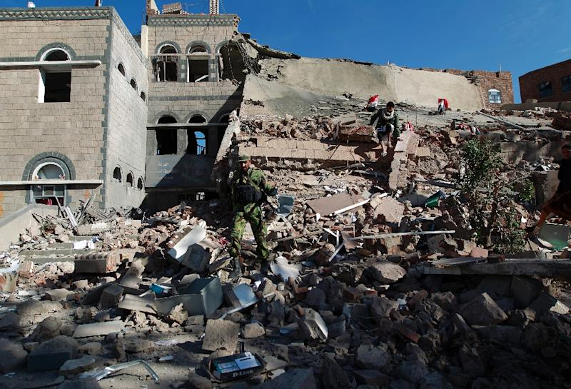 Yemenis check the rubble of the building of the Chamber of Commerce and Industry which was destroyed during air strikes on the capital, Sanaa, on January 5, 2016