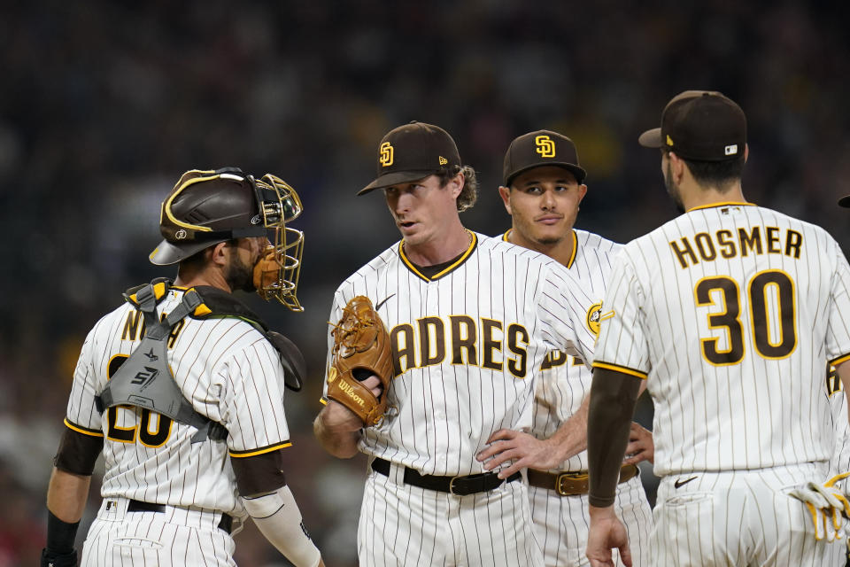 San Diego Padres relief pitcher Tim Hill, second from left, talks with catcher Austin Nola, left, during the eighth inning of a baseball game against the Philadelphia Phillies, Saturday, Aug. 21, 2021, in San Diego. (AP Photo/Gregory Bull)