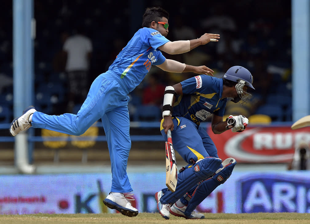 Indian cricketer Suresh Raina (L) collides with Sri Lankan batsman Lahiru Thirimanne as he tries to field the ball during the final match of the Tri-Nation series between India and Sri Lanka at the Queen's Park Oval stadium in Port of Spain on July 11, 2013. India won the toss and elected to field first. AFP PHOTO/Jewel Samad
