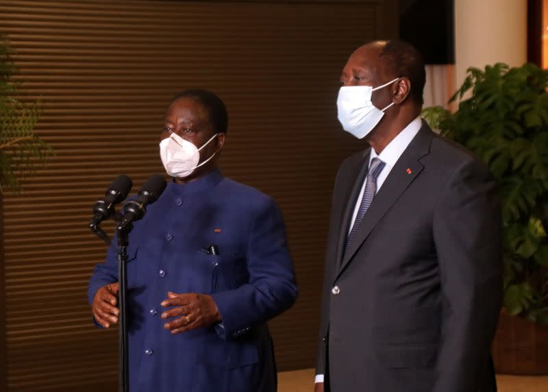 Ivory Coast former president Henri Konan Bedie talks while he stands with Ivory Coast President Alassane Ouattara during a meeting to initiate a post-election dialogue in Abidjan