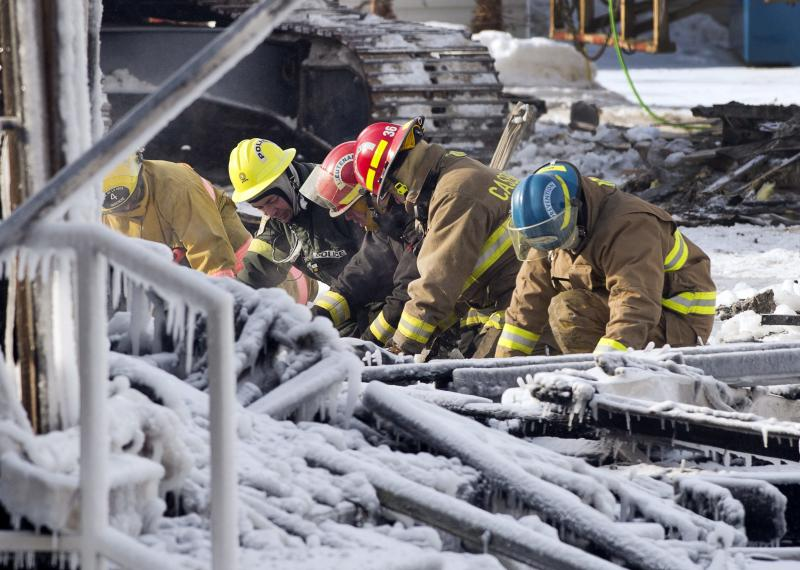 Rescue personnel search through the icy rubble of a fire that destroyed a seniors' residence Friday, Jan. 24, 2014, in L'Isle-Verte, Quebec. Five people are confirmed dead and 30 people are still missing, while with cause of Thursday morning's blaze is unclear police said. Authorities are using steam to melt the ice and to preserve any bodies that are buried. (AP Photo/The Canadian Press, Ryan Remiorz)