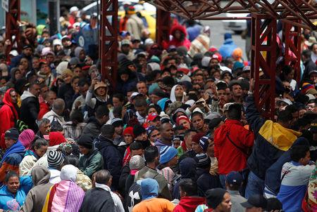 Venezuelan migrants wait to register their exit from Colombia before entering into Ecuador, at the Rumichaca International Bridge