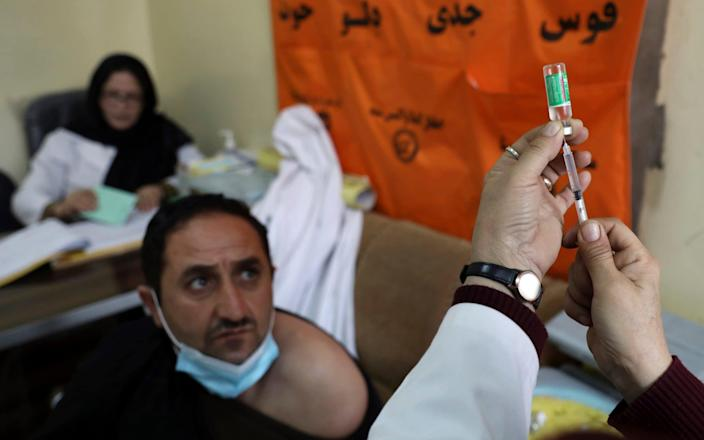 A man waits to be given the AstraZeneca vaccine at a hospital in Kabul, Afghanistan - Rahmat Gul/AP