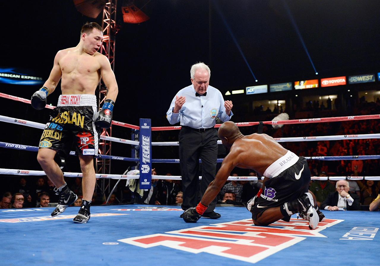 CARSON, CA - MARCH 16:  WBO Welterweight Champion Timothy Bradley (R) is knocked down in the first round by contender Ruslan Provodnikov as referee Pat Ruseell (C) looks on during their WBO Welterweight Championship boxing match at The Home Depot Center on March 16, 2013 in Carson, California.  (Photo by Kevork Djansezian/Getty Images)
