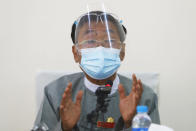 Myint Naing, a member of the Union Election Commission, wearing a protective face mask and shield gestures during a press conference in Naypyitaw, Myanmar, Tuesday, Oct. 20, 2020. Myanmar's official election supervisory body on Tuesday defended its decision to cancel voting in several areas in next month's election, saying it could not be free and fair because of ongoing conflicts with armed ethnic rebel groups. (AP Photo/Aung Shine Oo)
