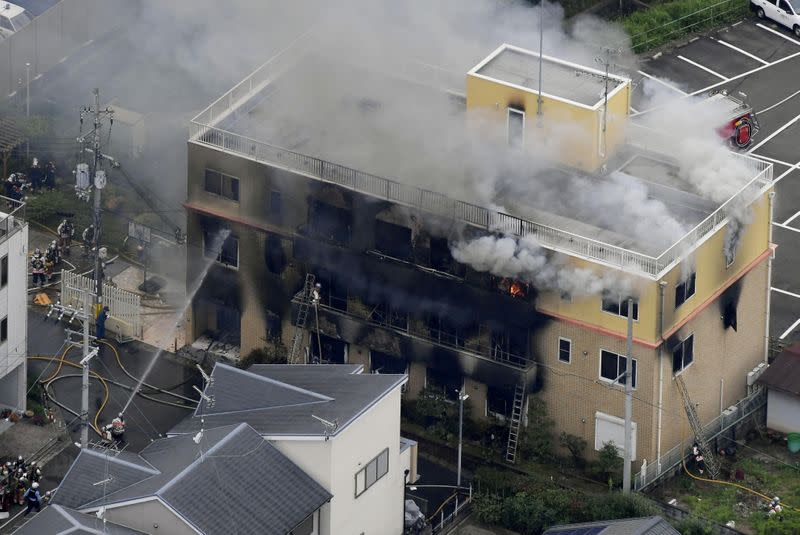 FILE PHOTO : An aerial view shows firefighters battling fires at the site where a man started a fire after spraying a liquid at a three-story studio of Kyoto Animation Co. in Kyoto, western Japan, in this photo taken by Kyodo
