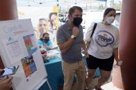 FILE - In this May 7, 2021, file photo, Rep. Ruben Gallego, D-Ariz., left, is joined by Kristin Urquiza, right, as they speak at a pop-up informational tent increasing efforts to bring more vaccine doses into Latino neighborhoods at a local shopping plaza in Phoenix. Arizona on Friday, Aug. 27, surpassed the milestone of 1 million confirmed coronavirus cases after the state reported new infections amid continued wrangling over vaccinations and mask requirements. (AP Photo/Ross D. Franklin, File)