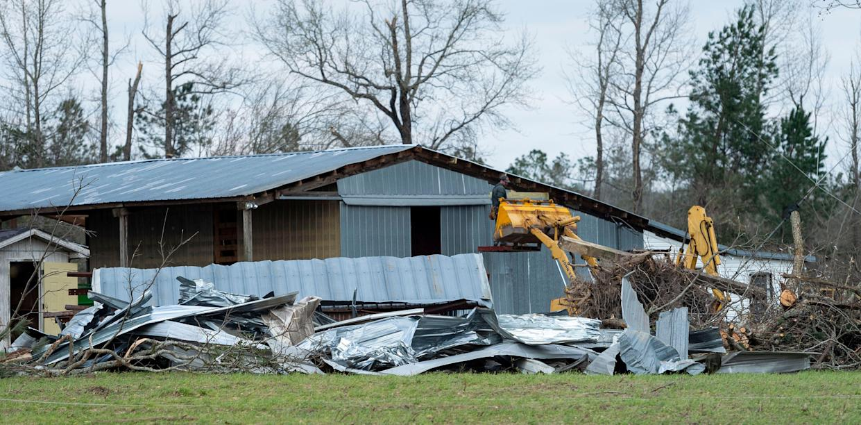 An emergency worker inspects damage seen on Lee County Road 11 near the intersection of Lee County Road 39, Monday, March 4, 2019, in Beauregard, Ala.