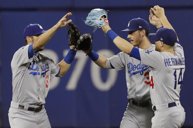 Los Angeles Dodgers left fielder Chris Taylor, left, center fielder Cody Bellinger, center, and Dodgers right fielder Enrique Hernandez (14) celebrate the Dodgers' 3-2 victory over the New York Mets in a baseball game, Sunday, Sept. 15, 2019, in New York. (AP Photo/Kathy Willens)
