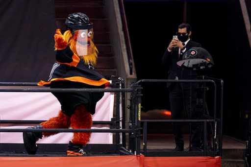 Philadelphia Flyers mascot Gritty tosses a large cap onto the ice for Travis Konecny's third goal of an NHL hockey game during the third period against the Pittsburgh Penguins, Friday, Jan. 15, 2021, in Philadelphia. (AP Photo/Chris Szagola)