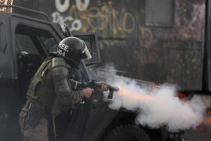 A riot police fires tear gas to disperse anti-government demonstrators in Santiago, Chile, Wednesday, Oct. 30, 2019. Chilean President Sebastián Pinera cancelled two major international summits after nearly two weeks of nationwide protests over economic inequality that have left at least 20 dead and damaged businesses and infrastructure around the country.(AP Photo/Esteban Felix)