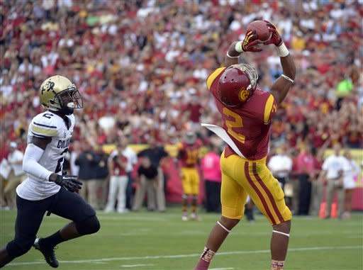 Southern California wide receiver Robert Woods, right, catches a pass for a touchdown as Colorado defensive back Kenneth Crawley defends during the first half of an NCAA college football game, Saturday, Oct.20, 2012, in Los Angeles. With that catch, Woods broke the USC receptions record. (AP Photo/Mark J. Terrill)