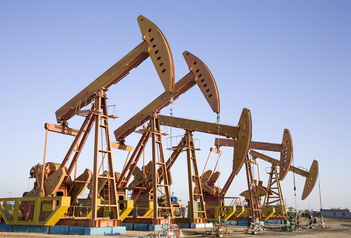 A row of oil pumps in a desert landscape