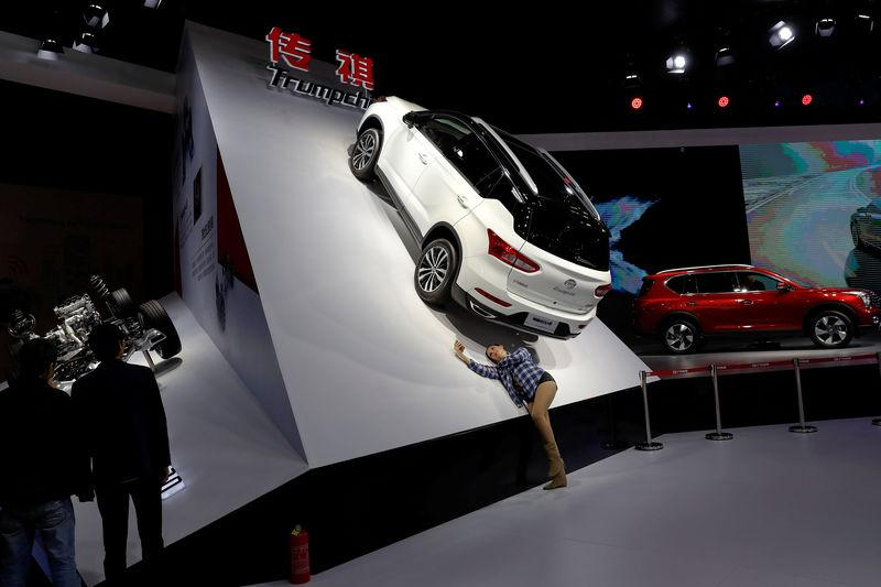 Woman takes pictures of Trumpchi GS4 from GAC Group displayed at the auto show in Shanghai