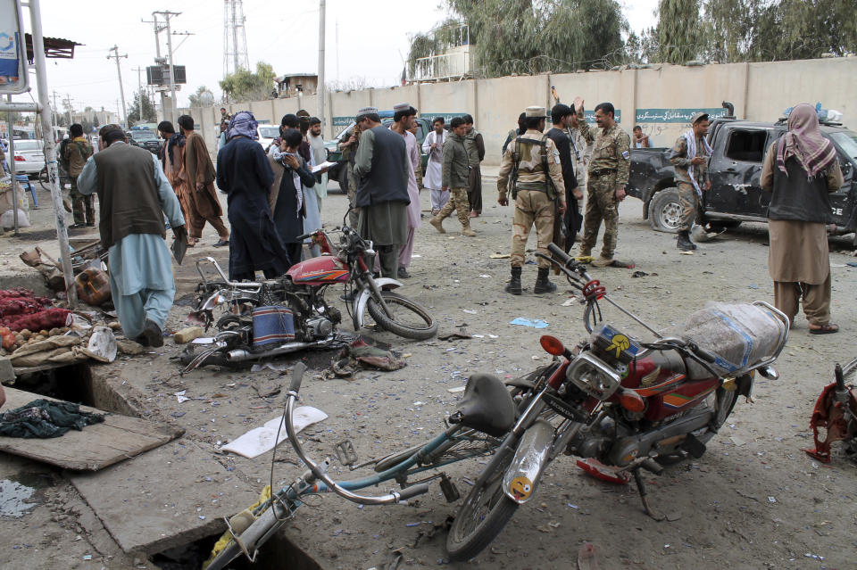 Security personnel inspect the site of a deadly roadside bomb explosion in Helmand province, southern Afghanistan, Sunday, Feb. 21, 2021. Two separate roadside bomb explosions in Afghanistan on Sunday killed and wounded numerous people. (AP Photo/Abdul Khaliq)