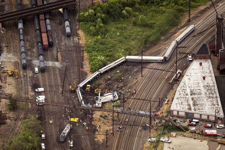 FILE PHOTO: Emergency workers look through the remains of a derailed Amtrak train in Philadelphia, Pennsylvania