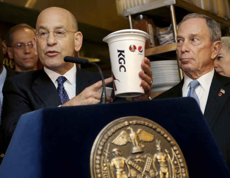 FILE- In this March 12, 2013 file photo, Montefiore Hospital President and CEO Steven Safyer, left, talks about large sugary drinks while New York City Mayor Michael Bloomberg looks on during a news conference at Lucky's Cafe in New York. A state appeals court panel peppered a city lawyer with tough questions during a Manhattan court session, Tuesday, June 11, 2013, aimed at determining whether New York City health officials exceeded their authority in placing a 16-ounce limit on most sweetened beverages at city-licensed eateries. (AP Photo/Seth Wenig, File)