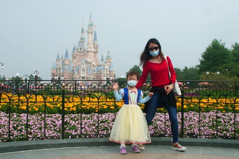 A young visitor, wearing face masks, waves at the Disneyland theme park in Shanghai as it reopened after the coronavirus closure, Monday, May 11, 2020. Visits will be limited initially and must be booked in advance, and the company said it will increase cleaning and require social distancing in lines for the various attractions.(AP Photo/Sam McNeil)