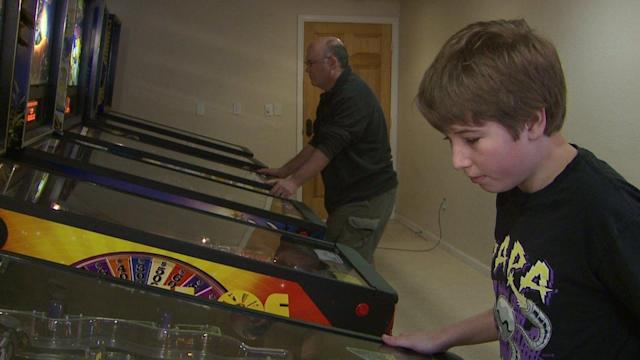 Escher and Adam play pinball together at their home (FOX31 Denver/KDVR)