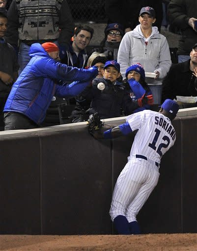 Chicago Cubs' Alfonso Soriano (12) is unable to catch a foul ball off the bat of St. Louis Cardinals' Carlos Beltran during the fourth inning of a baseball game Monday, April 23, 2012, in Chicago. (AP Photo/Jim Prisching)