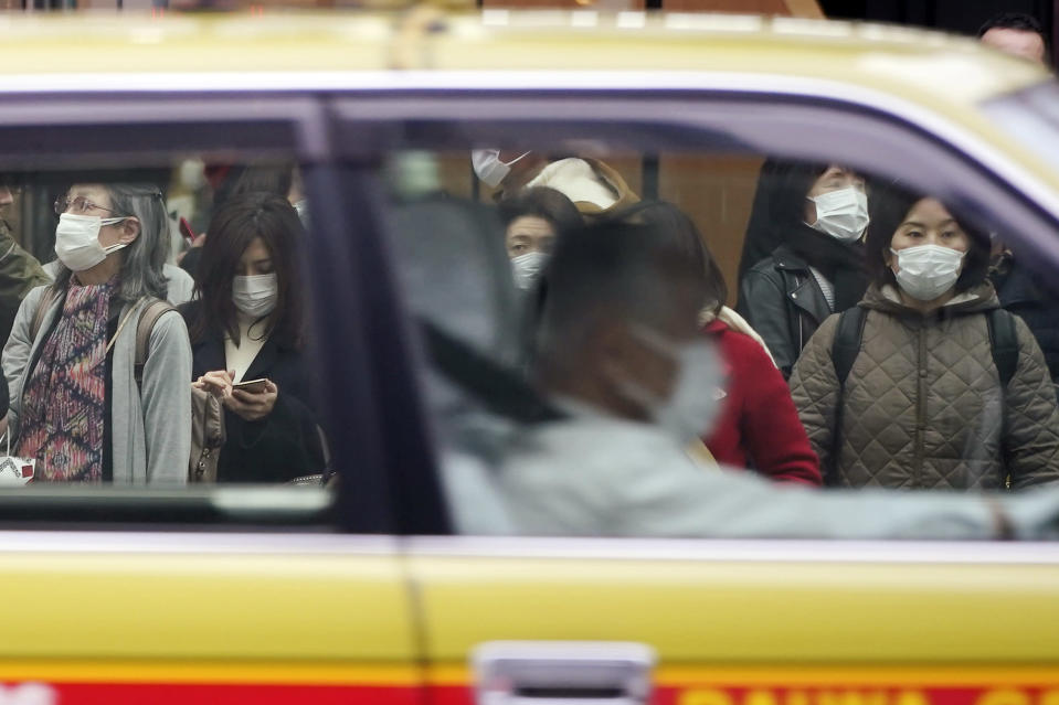 A taxi drives past pedestrians wearing masks as they wait at traffic light in Ginza shopping district Wednesday, Feb. 26, 2020, in Tokyo. At a government task force meeting Wednesday on the virus outbreak, Prime Minister Abe said he was asking organizers to cancel or postpone major sports or cultural events over the next two weeks. (AP Photo/Eugene Hoshiko)