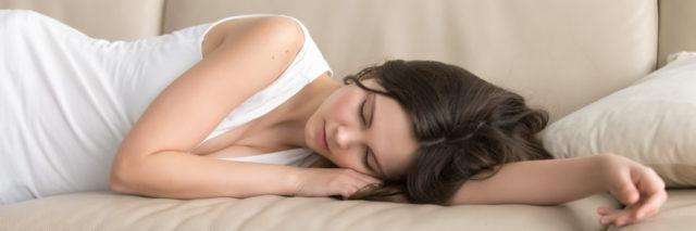 a woman lying asleep on her couch