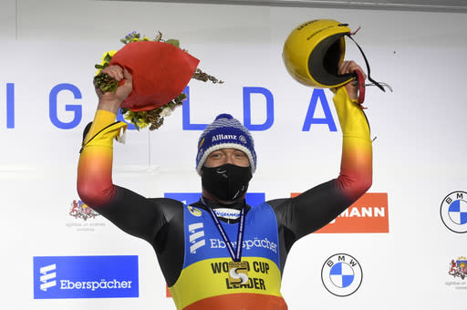 Felix Loch of Germany wearing a face mask to protect against coronavirus, celebrates on the podium after he finished first in a men's race at the Luge World Cup event in Sigulda, Latvia, Saturday, Jan. 9, 2021. (AP Photo/Roman Koksarov)