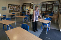Year 6 teacher Jane Cooper uses a 2 meter length of ruler and pipe to check seat spacings in her classroom as measures are taken to prevent the transmission of coronavirus before the possible reopening of Lostock Hall Primary school in Poynton near Manchester, England, Wednesday May 20, 2020. (AP Photo/Jon Super)