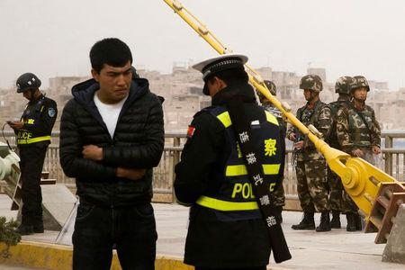 FILE PHOTO: A police officer checks the identity card of a man as security forces keep watch in a street in Kashgar