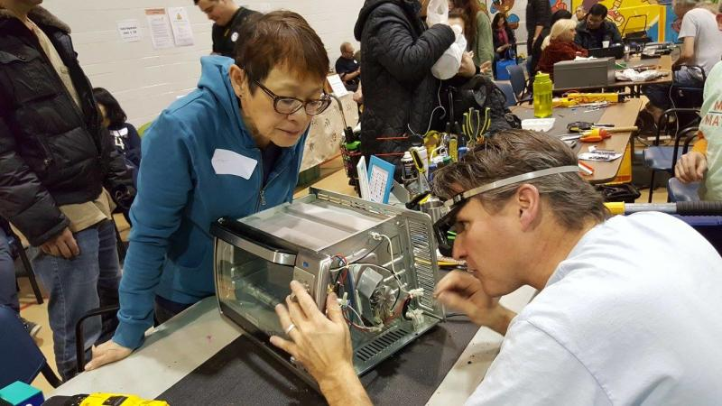 A woman looks on while her toaster oven undergoes repairs at a Toronto Repair Cafe event. (Toronto Repair Cafe/Facebook)