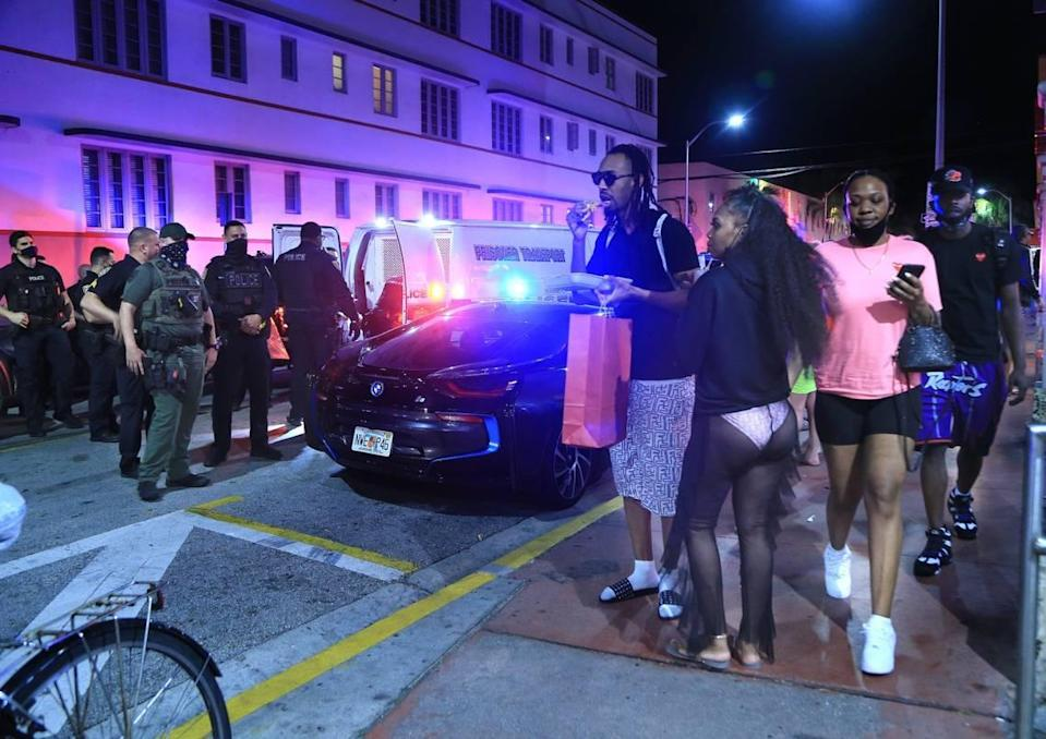 People watch as City of Miami Beach Police officers arrest several males on Ocean Drive and 10th Street as spring break officially began and the city expected thousands of tourists to visit South Beach, escaping cold weather and harsh COVID-19 restrictions on Saturday, February 20, 2021.