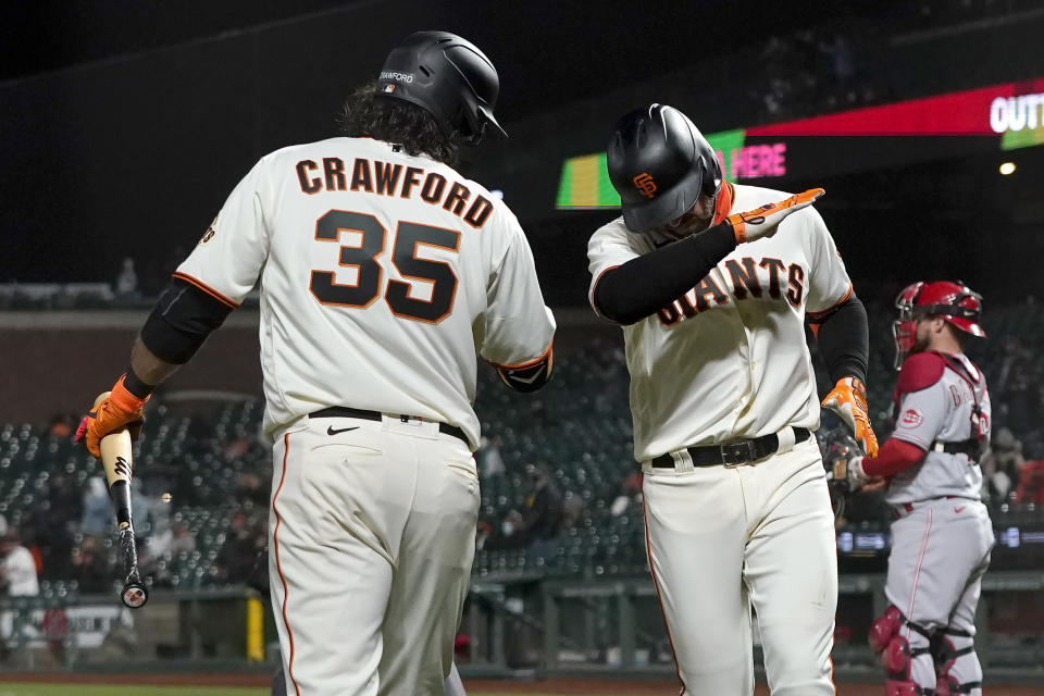 San Francisco Giants' Evan Longoria, right front, celebrates his solo home run with Brandon Crawford (35) during the sixth inning of a baseball game against the Cincinnati Reds in San Francisco, Tuesday, April 13, 2021. (AP Photo/Jeff Chiu)