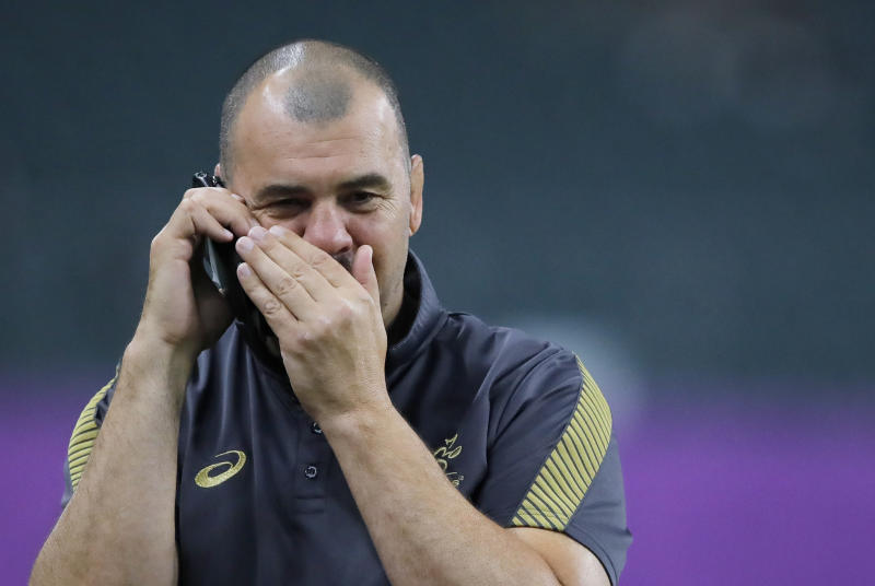 Australia's coach Michael Cheika gives a phone call during a training session in Oita, Japan, Friday Oct. 18, 2019. Australia will face England in the quarterfinals at the Rugby World Cup on Oct. 19.(AP Photo/Christophe Ena)