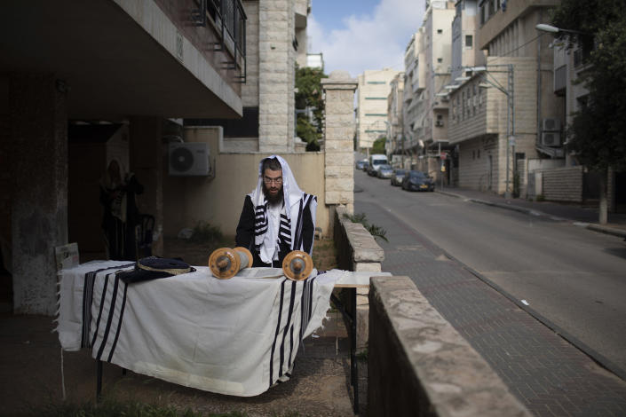 Image: An Ultra-Orthodox Jew prays a morning prayer next to his house as synagogues are closed following the government's measures to help stop the spread of the coronavirus, in Bnei Brak (Oded Balilty / AP)