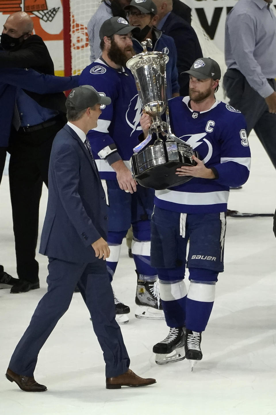 Tampa Bay Lightning center Steven Stamkos (91) holds up the Prince of Wales trophy for head coach Jon Cooper after defeating the New York Islanders during Game 7 of an NHL hockey Stanley Cup semifinal playoff series Friday, June 25, 2021, in Tampa, Fla. (AP Photo/Chris O'Meara)