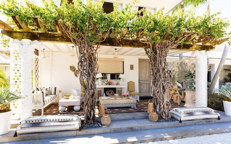 """<p>Flanked by blooming bougainvillea and stand-out roots, this dining terrace designed by Toronto-based designer <a href=""""http://www.colettevandenthillart.com/"""" rel=""""nofollow noopener"""" target=""""_blank"""" data-ylk=""""slk:Colette van den Thillart"""" class=""""link rapid-noclick-resp"""">Colette van den Thillart</a> embraces the whimsical flourishes of Palm Beach living. The custom hand-loomed outdoor carpet from New Moon Rugs features floral vines that lead to the mischievous monkey side table by <a href=""""https://circawho.com/"""" rel=""""nofollow noopener"""" target=""""_blank"""" data-ylk=""""slk:Circa Who"""" class=""""link rapid-noclick-resp"""">Circa Who</a>. </p>"""