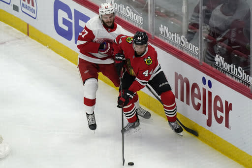 Chicago Blackhawks defender Calvin de Haan, right, controls the puck next to Detroit Red Wings center Michael Rasmussen during the third period of an NHL hockey game in Chicago, Friday, Jan. 22, 2021. The Blackhawks won 4-1. (AP Photo/Nam Y. Huh)