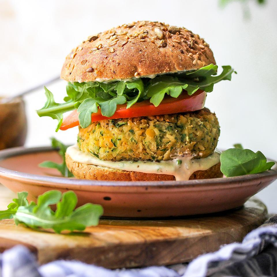 """<p>This vegan burger recipe is one you'll want to make again and again. Savory chickpea and zucchini patties are topped with a creamy, herb-flecked tahini ranch sauce, juicy tomato slices and peppery arugula for a satisfying and healthy homemade veggie burger. Serve them on buns or stuff them in pitas. We recommend making extra sauce--it's a great dip for veggie sticks and, thinned with a little water, it makes a wonderful salad dressing. <a href=""""http://www.eatingwell.com/recipe/273894/zucchini-chickpea-veggie-burgers-with-tahini-ranch-sauce/"""" rel=""""nofollow noopener"""" target=""""_blank"""" data-ylk=""""slk:View recipe"""" class=""""link rapid-noclick-resp""""> View recipe </a></p>"""