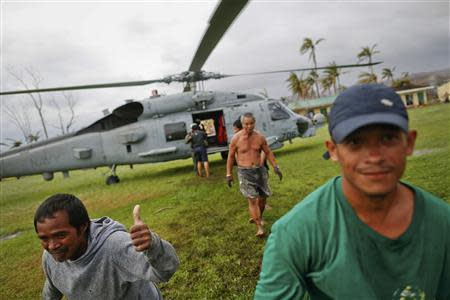 A survivor of Typhoon Haiyan gestures after receiving aid delivered by a U.S. military helicopter to a isolated village north of Tacloban November 17, 2013. REUTERS/Damir Sagolj