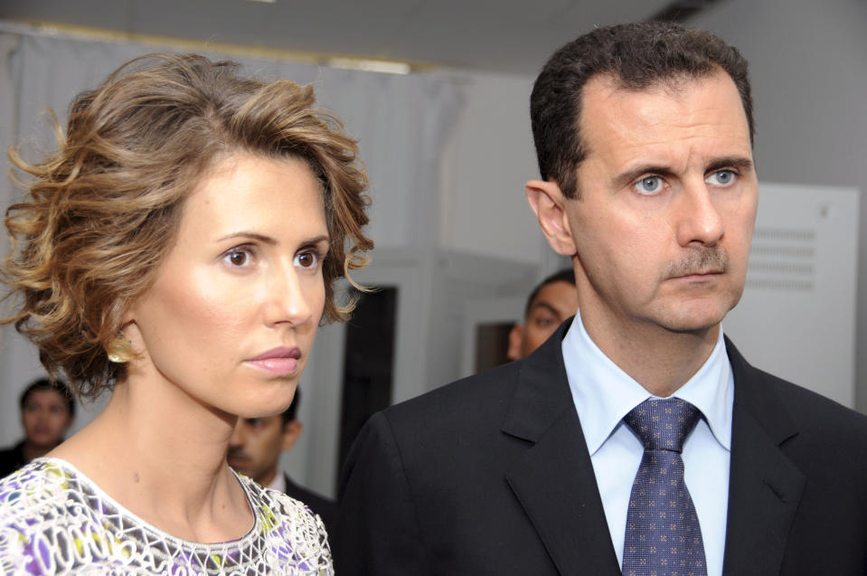 FILE - In this July, 13, 2010 file photo, Syrian President Bashar Assad, left, and his wife Asma Assad, listen to explanations as they visit a technology plant in Tunis, Tunisia. Assad's office said Wednesday, March 17, 2021, the country's first couple are on their way to recovery nine days after they tested positive for coronavirus. The presidency said that Assad and his wife have had mild symptoms of the illness and are continuing their work as usual from home and will return to normal life once they test negative to COVID-19 (AP Photo/Hassene Dridi, File)