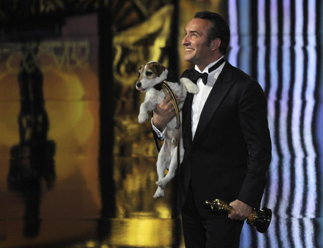 "Jean Dujardin holds Uggie after accepting the Oscar for best picture for ""The Artist"" during the 84th Academy Awards on Monday, Feb. 27, 2012. (AP Photo/Mark J. Terrill)"