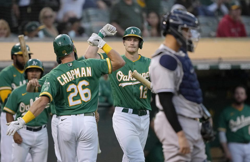 Oakland Athletics' Matt Chapman (26) is congratulated by Sean Murphy (12) after hitting a solo home run against the New York Yankees during the third inning of a baseball game Thursday, Aug. 26, 2021, in Oakland, Calif. (AP Photo/Tony Avelar)