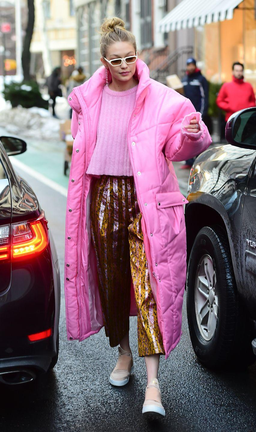 <p>Gigi just beat her record for craziest outfit in a Pepto pink sweater, metallic printed pants, and a sleeping bag with arms. I aspire to be this level of extra. </p>