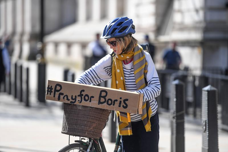 A cyclist with a sign reading '#PrayforBoris' rides through Westminster. (Photo: Peter Summers via Getty Images)
