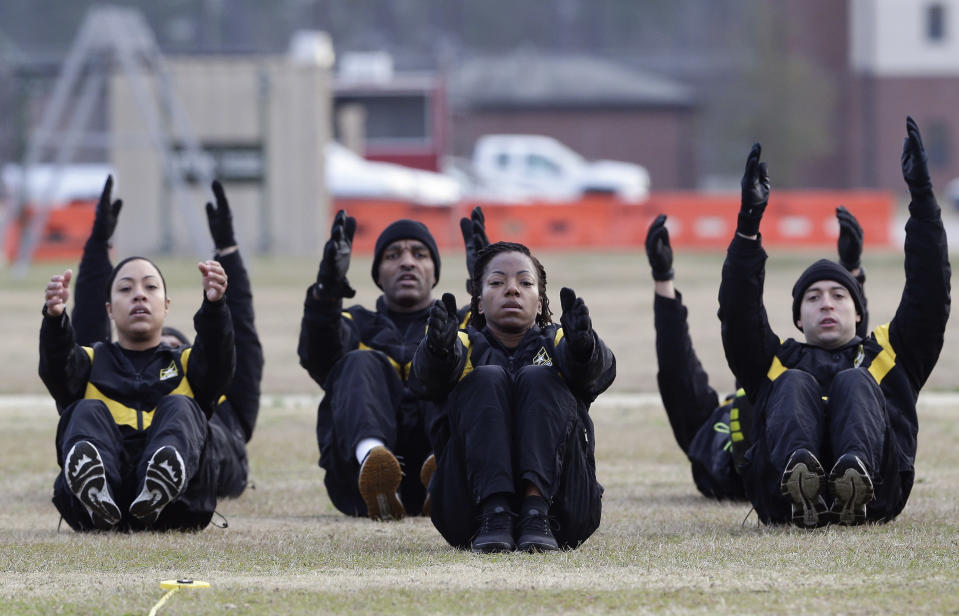 FILE - In this Jan. 8, 2019, file photo, U.S Army troops in training to become instructors participate in the new Army combat fitness test at the 108th Air Defense Artillery Brigade compound at Fort Bragg, N.C. Army leaders are kicking out the requirement that soldiers do at least one leg tuck as part of the new physical fitness test, after finding many troops — particularly women — were unable to do the exercise that requires them to raise their knees while hanging from a bar. (AP Photo/Gerry Broome, File)