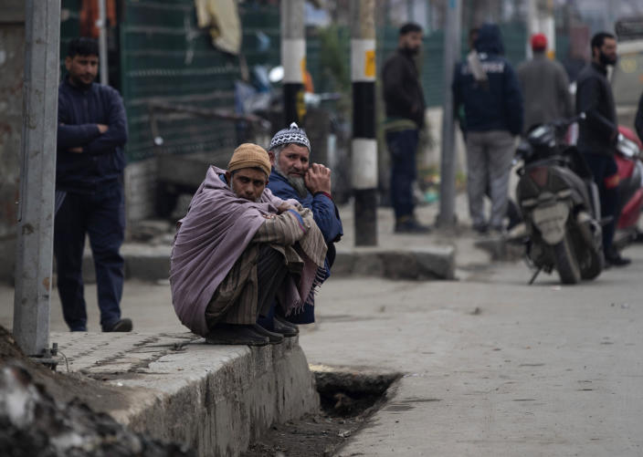 Elderly Kashmiri men rest on a pavement outside a taxi stand in Srinagar, Indian controlled Kashmir, Tuesday, Feb. 9, 2021. Businesses and shops have closed in many parts of Indian-controlled Kashmir to mark the eighth anniversary of the secret execution of a Kashmiri man in New Delhi. Hundreds of armed police and paramilitary soldiers in riot gear patrolled as most residents stayed indoors in the disputed region's main city of Srinagar. (AP Photo/Mukhtar Khan)