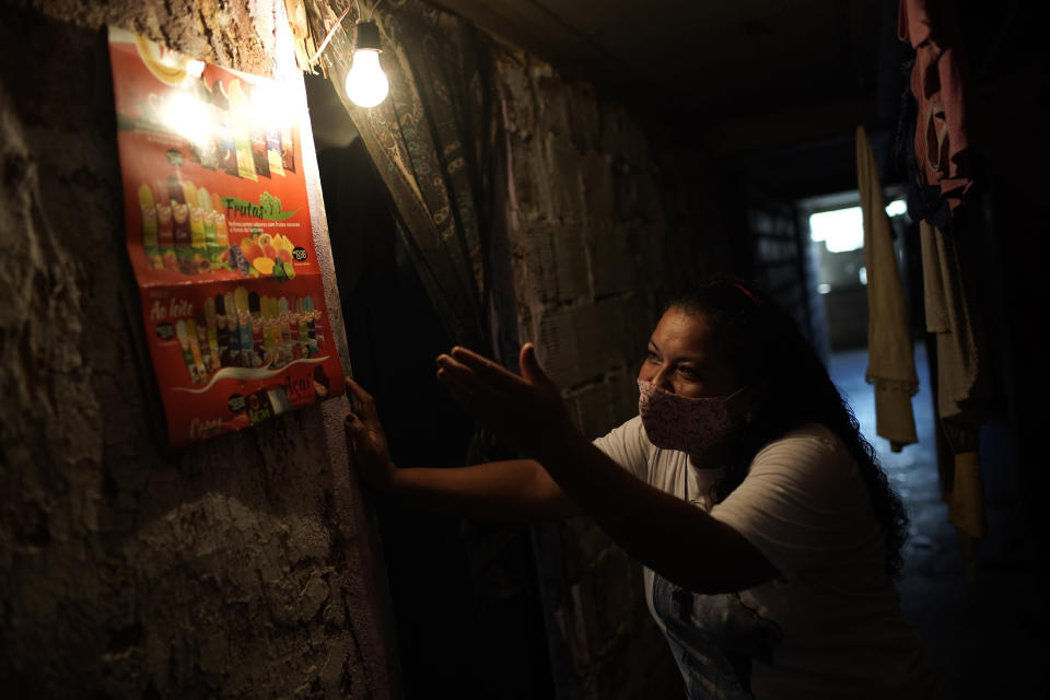 Informal worker Tassiana Nascimento Costa, who made a living hawking bottled water and sodas to tourists before the coronavirus pandemic hit, shows off a poster displaying the frozen treats she now sells to residents, posted inside the occupied building where she lives, in Rio de Janeiro, Brazil, Thursday, March 11, 2021. More than 6.5 million Brazilian women exited the workforce during the pandemic, dropping their participation rate below 48% - the least in more than a decade, according to official data published this month. (AP Photo/Silvia Izquierdo)