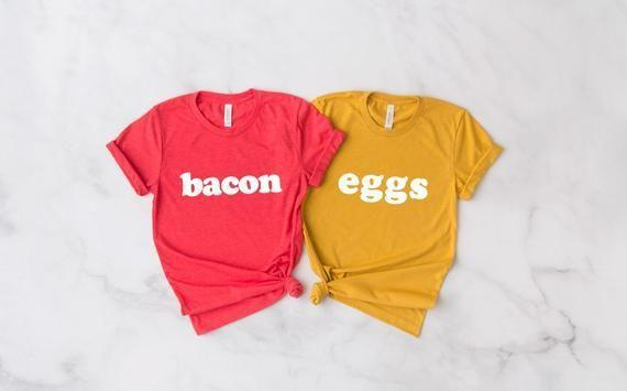 """<p><strong>TheMonogramLifeCo</strong></p><p>etsy.com</p><p><strong>$20.00</strong></p><p><a href=""""https://go.redirectingat.com?id=74968X1596630&url=https%3A%2F%2Fwww.etsy.com%2Flisting%2F742296199%2Fbacon-and-eggs-cursive-unisex-top-xs-xl&sref=https%3A%2F%2Fwww.countryliving.com%2Fdiy-crafts%2Fg21349110%2Fbest-friend-halloween-costumes%2F"""" rel=""""nofollow noopener"""" target=""""_blank"""" data-ylk=""""slk:Shop Now"""" class=""""link rapid-noclick-resp"""">Shop Now</a></p><p>Make it easy with these fun T-shirts. Pair the shirts with matching leggings, and you'll be dressed up in no time.</p>"""