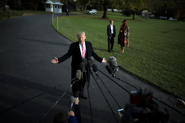 U.S. President Donald Trump talks with the reporters as First Lady Melania Trump and her son Barron wait for him while departing the White House for Palm Beach, in Washington D.C., U.S. November 21, 2017. REUTERS/Carlos Barria TPX IMAGES OF THE DAY